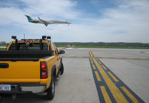 Car waiting on runway with plane landing